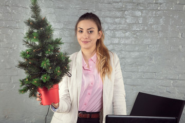 business woman poses for a photo with a Christmas tree