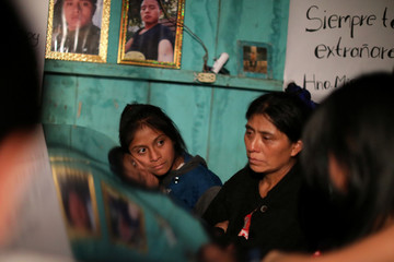 A girl lays her face on the coffin of Misael Paiz below his photos inside his family home at a wake in Aguacate
