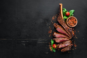 Photo sur Plexiglas Steakhouse Steak on the bone. tomahawk steak On a black wooden background. Top view. Free copy space.