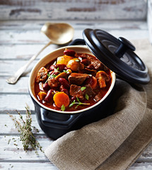 Beef goulash with mushrooms and vegetables. Symbolic image. Concept for a tasty and hearty dish. Bright wooden background