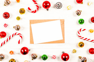 Letter to santa concept. Festive flat lay composition with blank invitation for new year celebration & craft paper envelope. Christmas greeting card template concept. Background, copy space, top view.