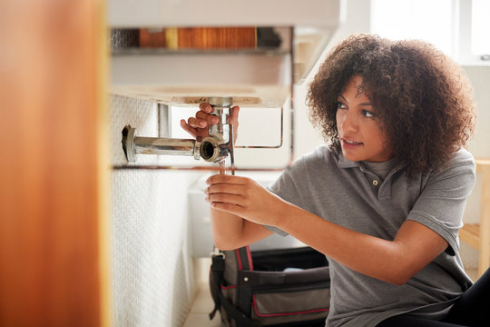 Young black female plumber sitting on the floor fixing a bathroom sink, seen from doorway