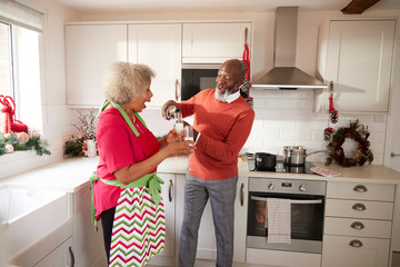 Senior black man pouring champagne for his partner in the kitchen while preparing dinner on Christmas Day, side view