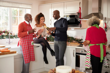 Multi-ethnic adult family celebrating  with champagne in the kitchen while preparing dinner on Christmas Day