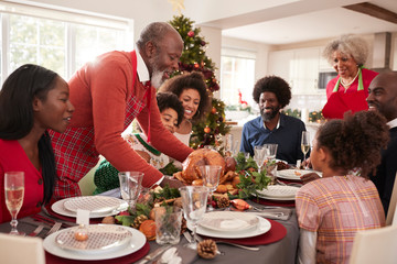 Grandfather bringing the roast turkey to the dinner table during a multi generation, mixed race family Christmas celebration, close up