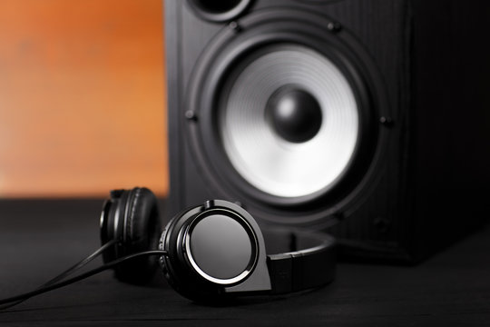 Photo of black music audio speaker and headphones. Close-up.