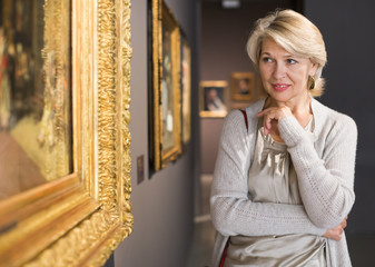 Mature woman in art museum near the painting