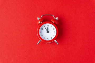 Creative flat lay vintage clock on red office table top view background concept clock on red paper color with copy space in minimal style, empty template for text, break workplace at noon for lunch.
