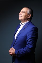 Beautiful older man in front of a colored background