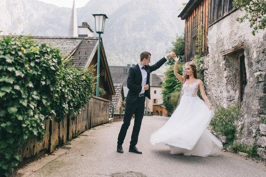 A beautiful wedding couple walks in a fairy Austrian town, Hallstatt.