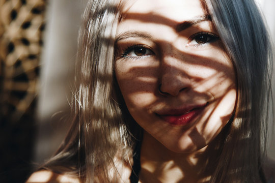 Young woman with shadow pattern on face