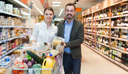 Adult couple is standing with cart with products