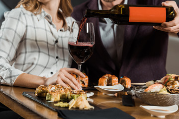 Partial view of man pouring red wine in glass while couple having dinner in restaurant