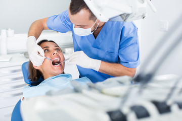 Dentist is treating patient which is sitting in dental chair in clinic