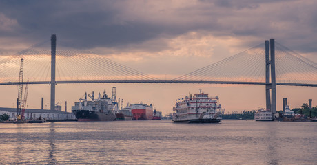 Waterfront of Savannah, Georgia, USA - July 22, 2018: A Riverboat Cruises as it leaves the Port of Savannah in Georgia at sunset