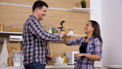 Young husband and wife fighting with kitchen tools and having fun. Casual night