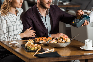 Partial view of couple sitting at table while man paying for dinner in restaurant