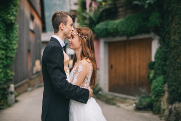 A beautiful wedding couple walks in a fairy Austrian town, Hallstatt.
