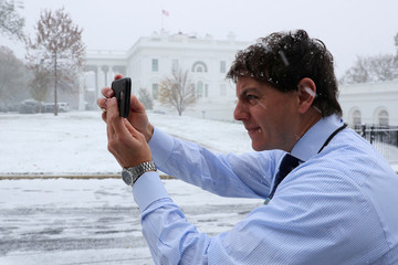 White House Deputy Press Secretary Gidley takes pictures at the White House in a light snow in Washington