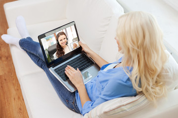 technology and communication concept - woman with laptop computer having video call with customer service operator at home