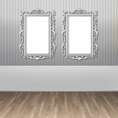 Two blank silver Baroque picture frames on gray lined wallpaper background