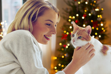 Fototapete - pets, holidays and people concept - happy young woman with cat in bed at home over christmas tree lights on background