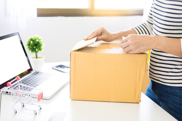 e-commerce delivery concept and online selling start up small business owner packing in the card box at workplace. freelance woman seller prepare product for packaging process at shop