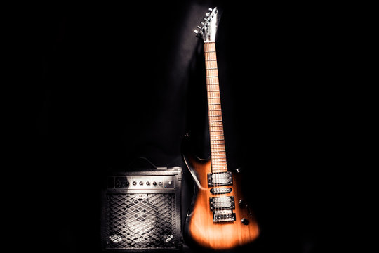 Electric guitar and amplifier isolated on a dark background.