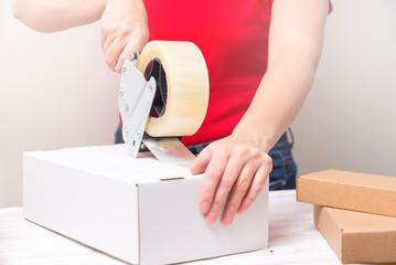 Woman packing cardboard boxes using tape dispenser