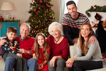 Portrait Of Multi Generation Family Sitting On Sofa In Lounge At Home On Christmas Day