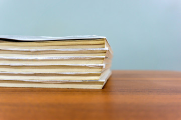 A stack of books are lying on a brown table, documents are stacked close-up.