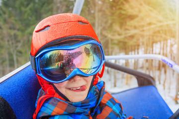 Portrait of Cute skier boy in a winter ski resort.