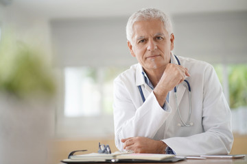 Portrait of smiling mature doctor looking at camera