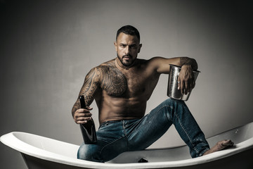 Champagne celebration. Handsome man with tattooed body on gray background. Sexy night party - young lovers. Fashion mans legs in jeans.