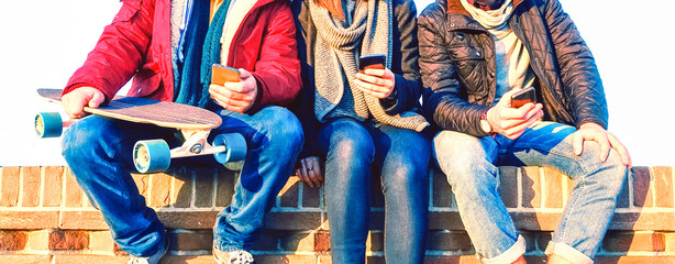 Group of friends using mobile phone sitting in row at winter time - Young people texting on smartphone - Teenagers holding cellphone outdoor - Concept of teens addicted to modern technology
