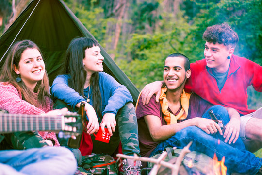Group of multiracial friends sitting at campfire playing music -  Happy multicultural teenagers having fun around fire drinking together on vacation - Concept of  friendship and outdoor activity