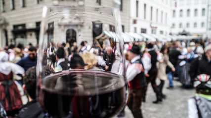 A glass of red wine and crowd of people on a st. Martin festival in Ljubljana