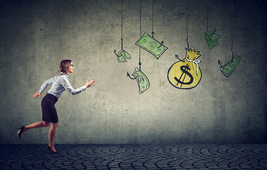 Business woman motivated by money hanging on a fishing hook.