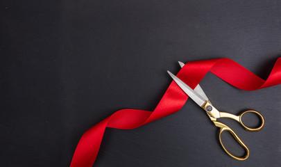 Scissors cutting red silk ribbon against black background