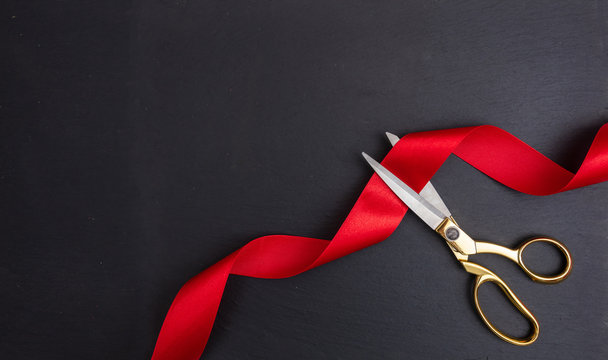 Scissors cutting red silk ribbon against black background