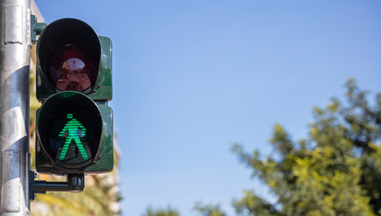 Green traffic lights for pedestrians, blue sky background Fotomurales