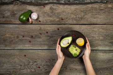 Woman hand holding wooden plate with piece of avocado, sandwitch with guacamole sauce and lemon on wooden rustik background