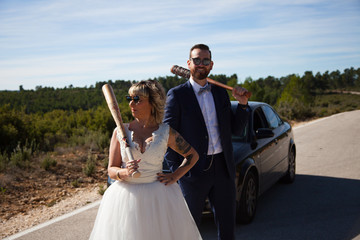 Couple of newlyweds stopped with the car on a lonely road wielding baseball bats