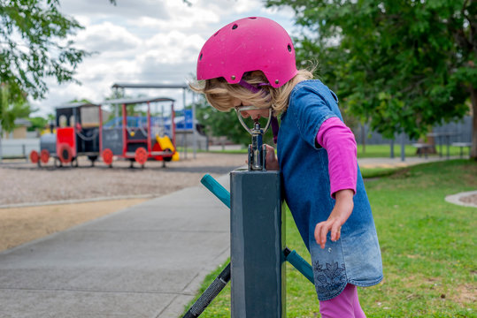 Young girl in pink outfit and pink helmet riding a kick-scooter in the park having a drink from fountain