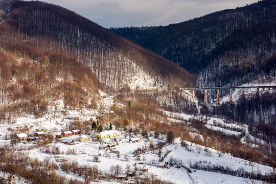 winter rail road transportation in mountains. station and village on hill and viaduct in the distance