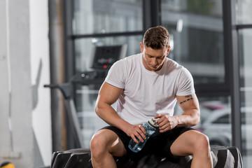 Fototapeta handsome athletic bodybuilder sitting on tire with sport bottle of water in gym obraz