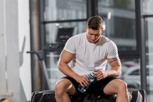 handsome athletic bodybuilder sitting on tire with sport bottle of water in gym