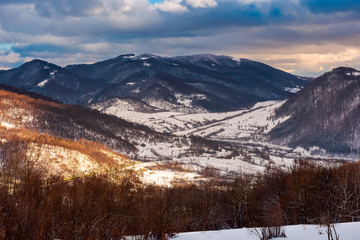 beautiful winter scenery of Carpathians. Village down in the valley in dappled light. gorgeous evening cloudy sky above the ridge.