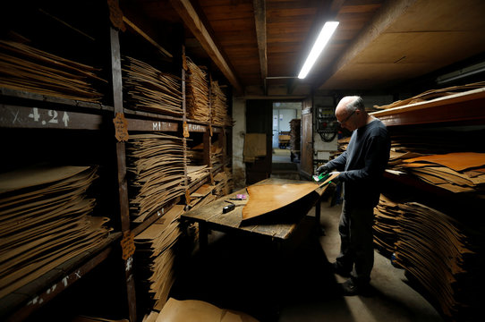 An employee works on a piece of leather to make shoes and boots at the Tannery Bastin of shoemaker J.M. Weston in Saint-Leonard-de-Noblat