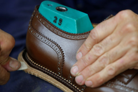 An employee works on sole of a leather shoe at the shoemaker J.M. Weston factory in Limoges